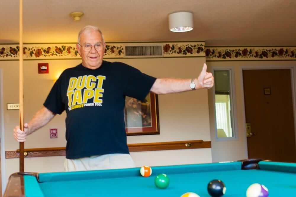 senior resident playing pool
