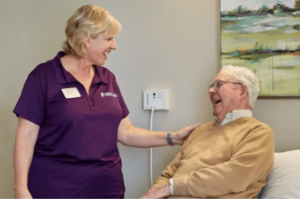 Nurse with hand on senior male shoulder laughing