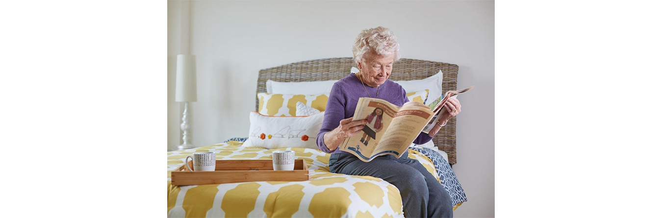 elderly woman reading the newspaper